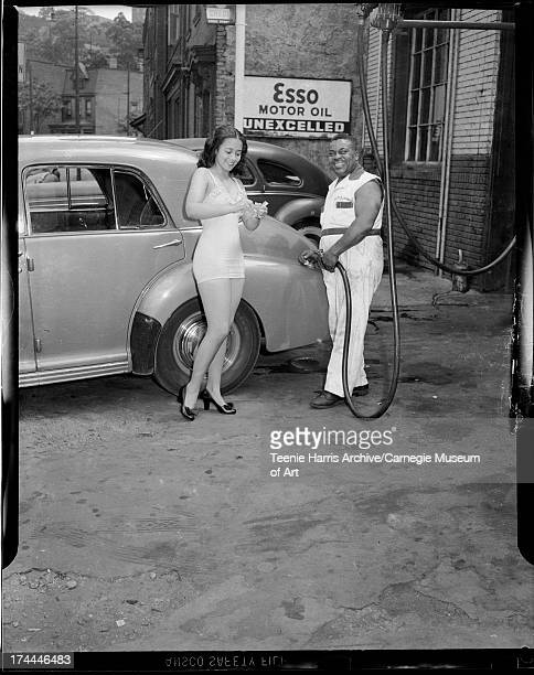 Vivian Clayton tearing up gasoline rationing stamps and Sam 'Scotty' Scott pumping gas Pittsburgh Pennsylvania August 1945