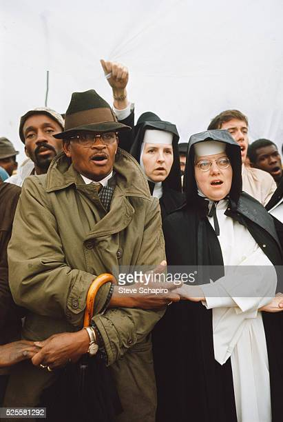 Vivian holding hands with a nun during a rally before beginning the march from Selma to Montgomery. They are marching to protest denial of voting...