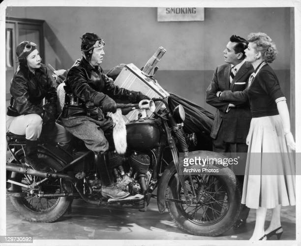 Vivian Vance and Bill Frawley ride in on a motorcycle in front of a dismayed Desi Arnaz and Lucille Ball in the television series 'I Love Lucy', 1951.