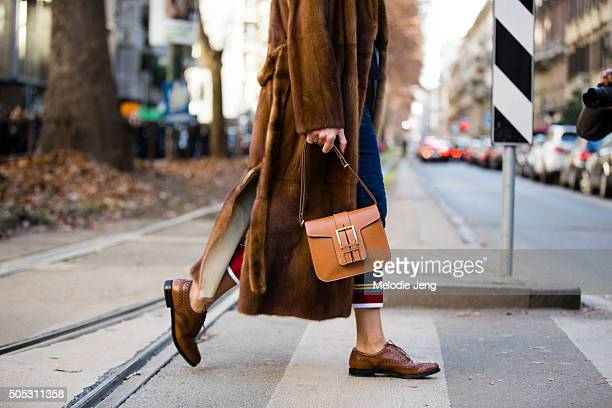 Viviana Volpicella wears a long brown fur coat with a brown leather purse and brown brogues during the Milan Men's Fashion Week Fall/Winter 2016/17...