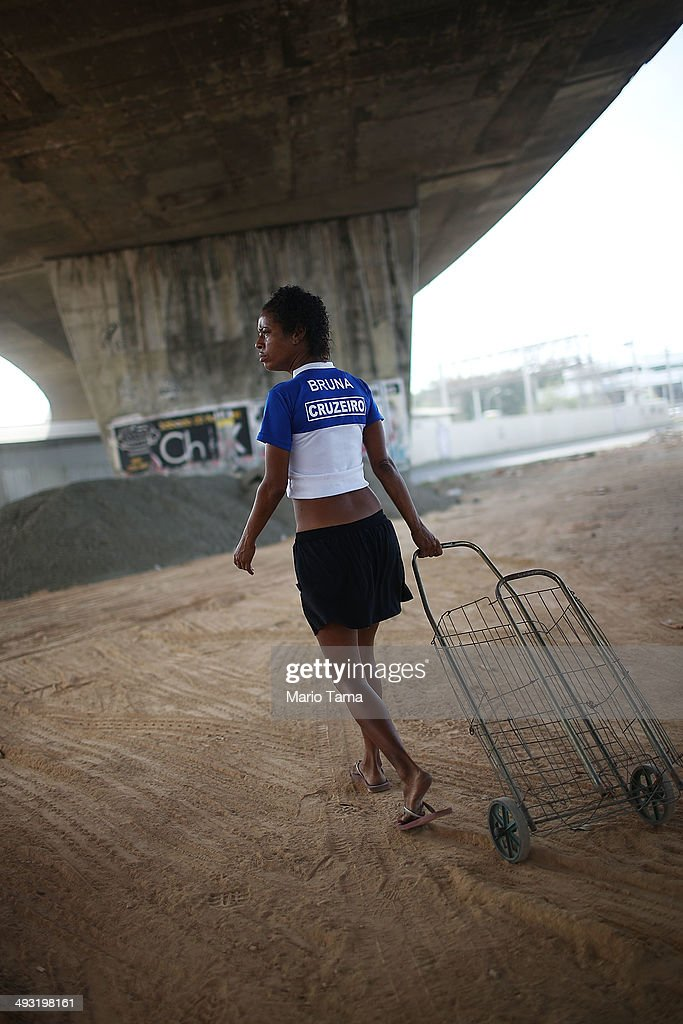 Viviane Sabino de Souza walks with her cart while searching for recyclable metal near her makeshift dwelling beneath a stretch of the Transcarioca BRT (Bus Rapid Transit) highway being constructed on May 22, 2014 in Rio de Janeiro, Brazil. De Souza says her parents were killed in flooding north of Rio de Janeiro, leaving her homeless last year. She has lived beneath the stretch of new highway for about six weeks and is awaiting government assistance for new identification papers. De Souza earns money partially by collecting recyclable materials discarded from construction of the highway. The Transcarioca is part of the larger BRT system being constructed which will link Rio's international airport with Barra da Tijuca, the main site of the Rio 2016 Olympic Games. The city is taking on a number of infrastructure projects ahead of the 2014 FIFA World Cup and Rio 2016 Olympic Games.