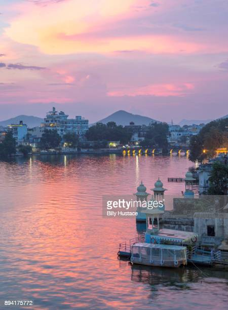 a vivid and colorful sunset reflected in lake pichola in the historical city of udaipur, india. - udaipur stock pictures, royalty-free photos & images