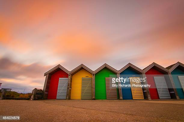 vivid coloured beach huts at sunset - northumberland stock pictures, royalty-free photos & images