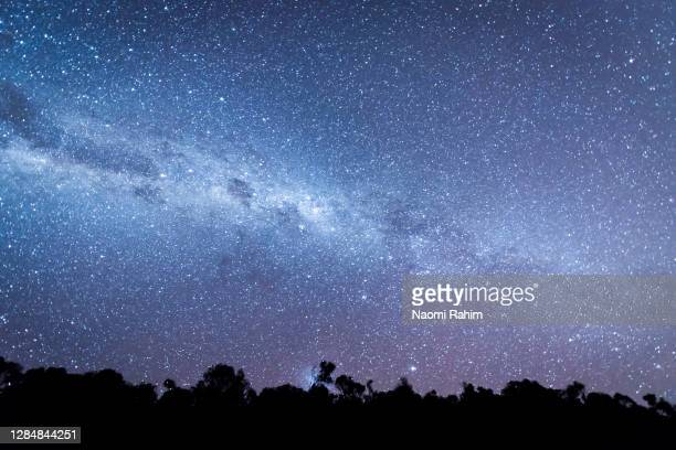 vivid milkyway surrounded by billions of stars in the night sky in australia - winter solstice stock pictures, royalty-free photos & images