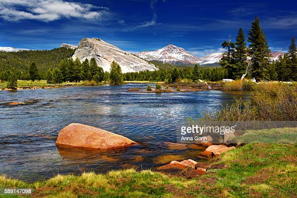 Vivid red rocks in Tuolumne River in Yosemite National Park with snowcapped mountains in distance, summer