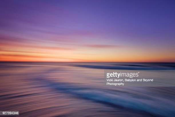 Vivid Sunrise Purples and Blurred Waves