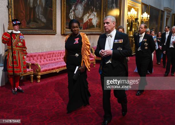 Vivien Hunt and Britain's Prince Andrew Duke of York arrive through the East Gallery during a State Banquet in the ballroom at Buckingham Palace in...