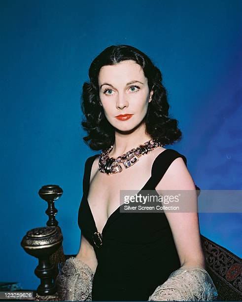Vivien Leigh British actress wearing a black dress with a plunging neckline and an ornate necklace in a studio portrait against a blue background...