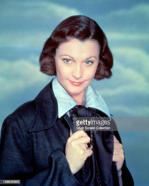 Vivien Leigh British actress wearing a dark blue jacket over a light blue shirt in a studio portrait against a background of blue sky and clouds...