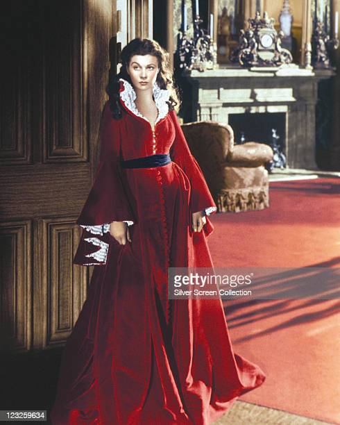 Vivien Leigh British actress wearing a long red dress trimmed with white lace with a black belt in a publicity portrait issued for the film 'Gone...