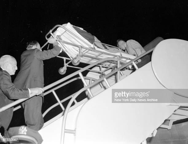 Vivien Leigh on stretcher heavily wrapped in blankets and carried from ambulance at Idlewilde Airport to airplane goes back to London