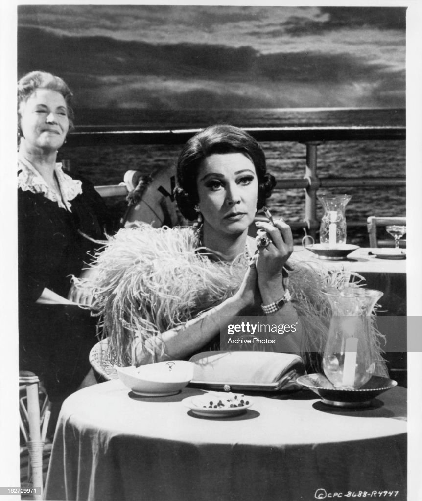 Vivien Leigh sitting at table on the deck in a scene from the film 'Ship Of Fools', 1965.