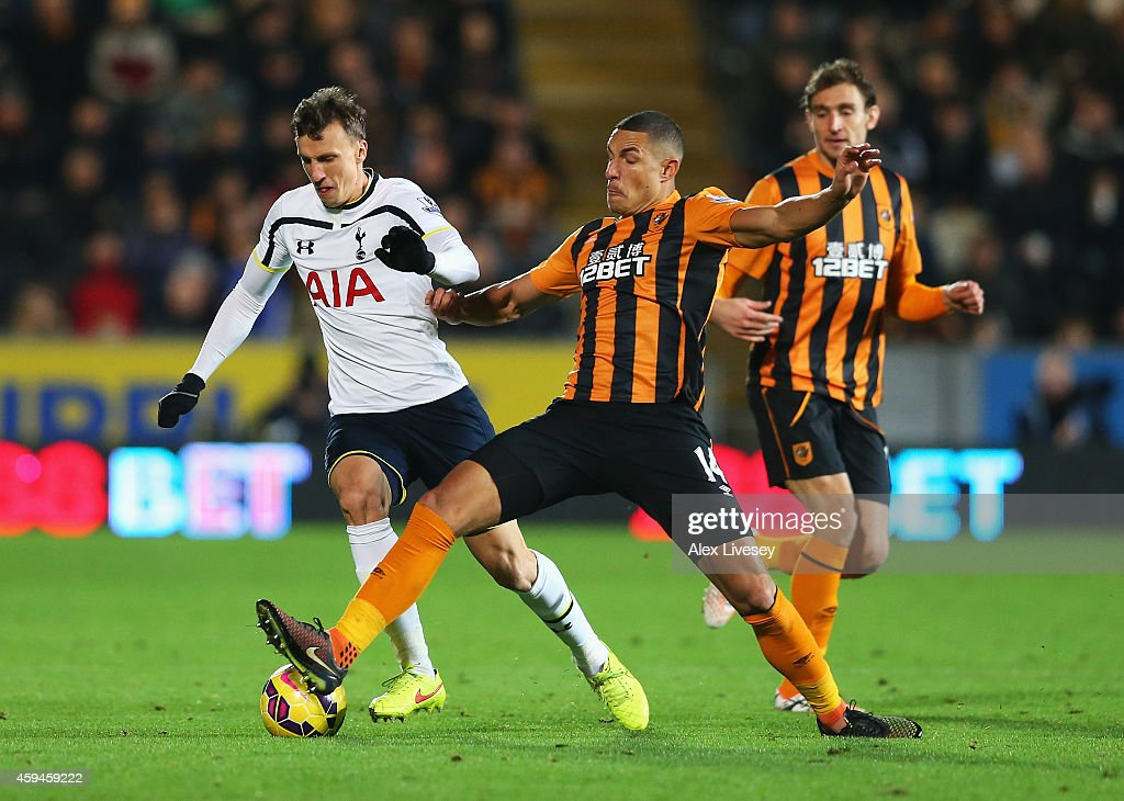 Vlad Chiriches of Tottenham Hotspur is tackled by Jake Livermore of Hull City during the Barclays Premier League match between Hull City and Tottenham Hotspur at KC Stadium on November 23, 2014 in Hull, England.
