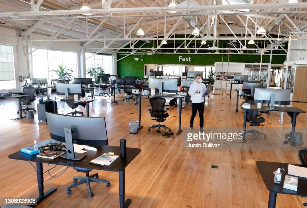 Vlad Lapich, with tech startup company Fast, walks by socially distanced desks in the office on March 24, 2021 in San Francisco, California. A...