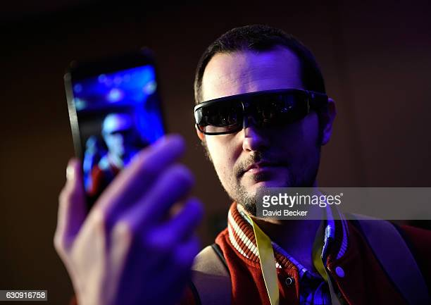 Vlad Savov of New York takes a selfie wearing the ODG R8 AR/VR smartglasses during a Qualcomm press event for CES 2017 at the Mandalay Bay Convention...