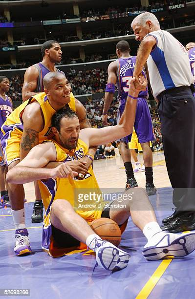 Vlade Divac of the Los Angeles Lakers gets helped off the ground by teammate Caron Butler and referee Bennett Salvatore during the game against the...