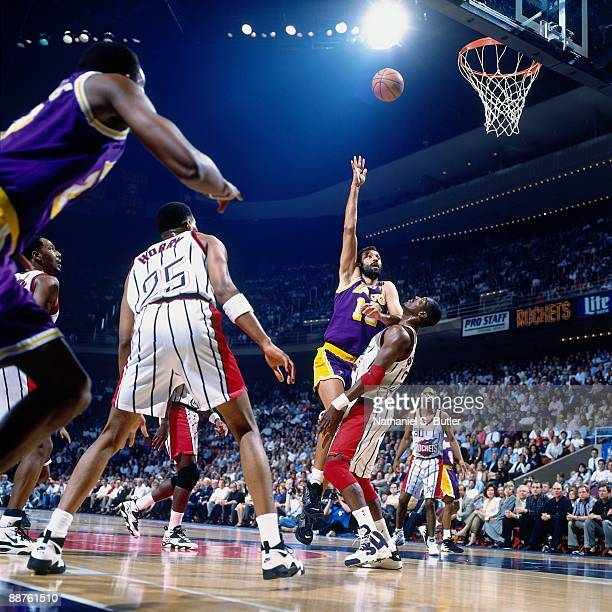 Vlade Divac of the Los Angeles Lakers shoots over Hakeem Olajuwon of the Houston Rockets in Game Three of the Western Conference Quarterfinals during...