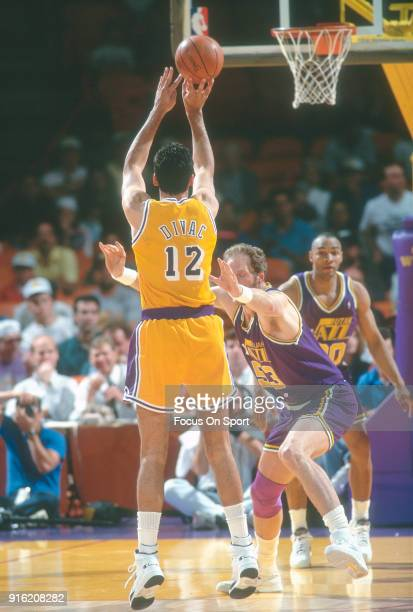 Vlade Divac of the Los Angeles Lakers shoots over Mark Eaton of the Utah Jazz during an NBA basketball game circa 1992 at The Forum in Inglewood...
