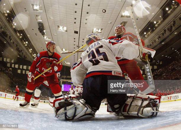 Vladimir Antipov and Alexei Yashin of Russia follow the puck with their eyes as a save is made by goaltender Jan Lasak of Slovakia chase the puck...