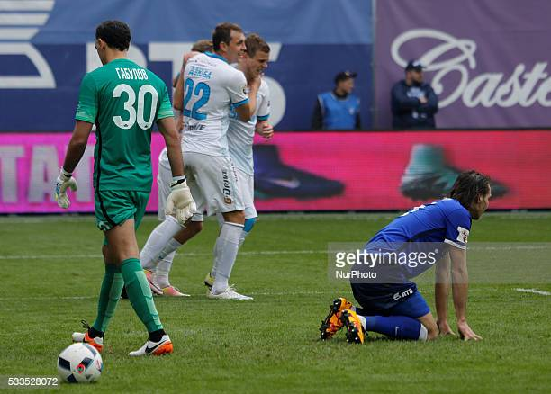 Vladimir Gabulov of FC Dynamo Moscow and Vitali Dyakov of FC Dynamo Moscow react as Artem Dzyuba of FC Zenit St Petersburg celebrates his goal with...