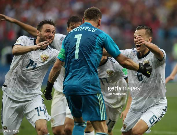 Vladimir Granat and Denis Cheryshev celebrates with goalkeeper Igor Akinfeev of Russia when they win the penalty shoot out during the 2018 FIFA World...