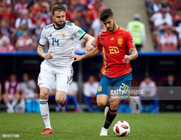 Vladimir Granat of Russia competes for the ball with Marco Asensio of Spain during the 2018 FIFA World Cup Russia Round of 16 match between Spain and...