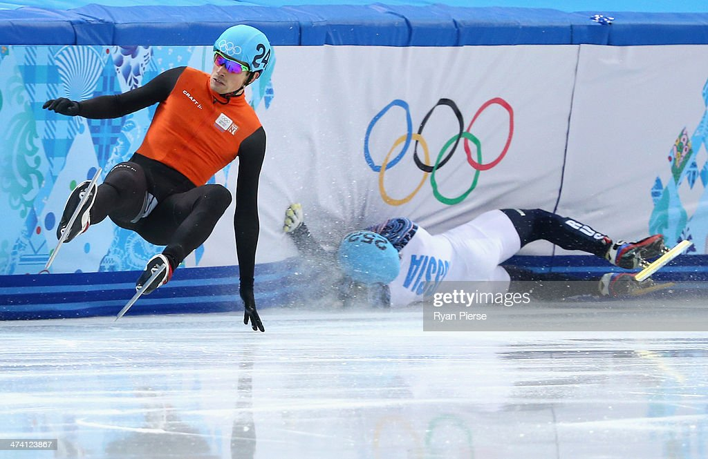 Vladimir Grigorev (R) of Russia hits the wall while Freek van der Wart (L) of the Netherlands falls in the Short Track Men's 500m Quarterfinals on day fourteen of the 2014 Sochi Winter Olympics at Iceberg Skating Palace on February 21, 2014 in Sochi, Russia.