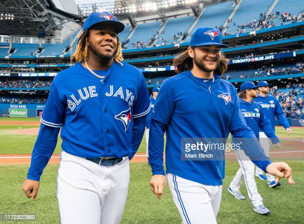 Vladimir Guerrero Jr. #27 and Bo Bichette of the Toronto Blue Jays walk off the field after defeating the Tampa Bay Rays in the last game of the...