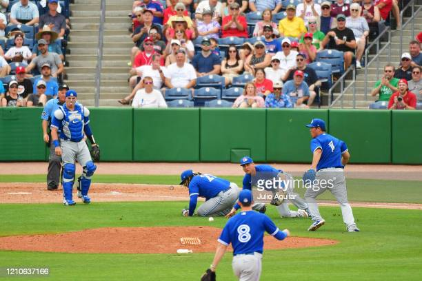 Vladimir Guerrero Jr #27 Andy Burns and Shun Yamaguchi of the Toronto Blue Jays miss a popup hit by Rhys Hoskins of the Philadelphia Phillies during...