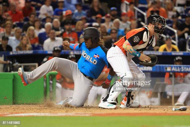 Vladimir Guerrero Jr #27 of the Toronto Blue Jays and the World Team slides past Zack Collins of the Chicago White Sox and the US Team to score in...