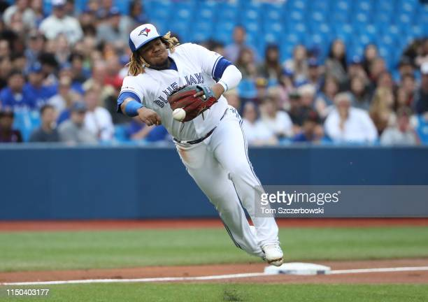 Vladimir Guerrero Jr #27 of the Toronto Blue Jays attempts unsuccessfully to throw out Wilfred Tovar of the Los Angeles Angels of Anaheim who hits an...