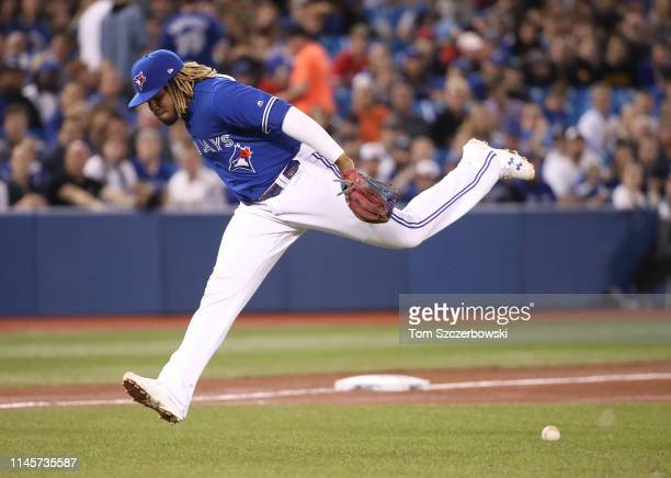 Vladimir Guerrero Jr #27 of the Toronto Blue Jays cannot pick up a soft infield single by Jackie Bradley Jr #19 of the Boston Red Sox as he overruns...