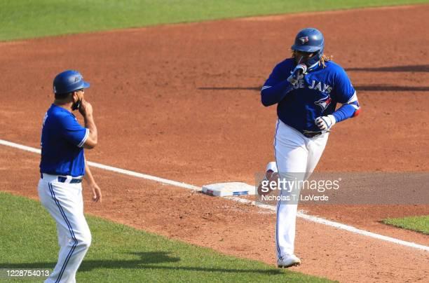 Vladimir Guerrero Jr. #27 of the Toronto Blue Jays celebrates his third inning home run with Blue Jays third base coach Louis Rivera at Sahlen Field...