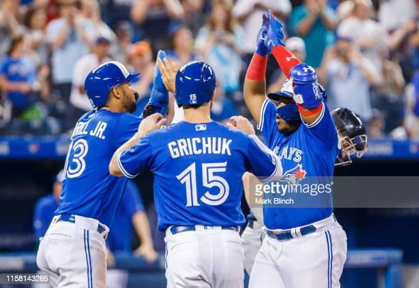 Vladimir Guerrero Jr #27 of the Toronto Blue Jays celebrates his three run home run with teammates Randal Grichuk and Lourdes Gurriel Jr #13 against...
