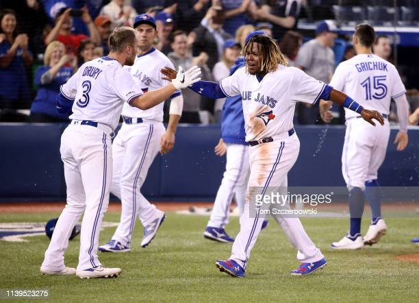 Vladimir Guerrero Jr. #27 of the Toronto Blue Jays celebrates their victory as Brandon Drury hit a game-winning two-run home run in the ninth inning...