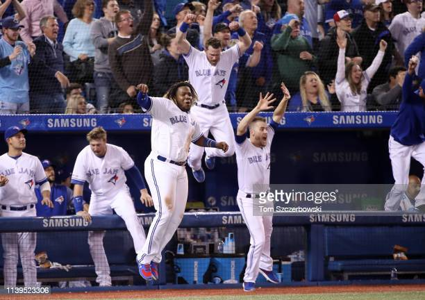 Vladimir Guerrero Jr. #27 of the Toronto Blue Jays celebrates their victory with Billy McKinney and Ken Giles as Brandon Drury hit a game-winning...