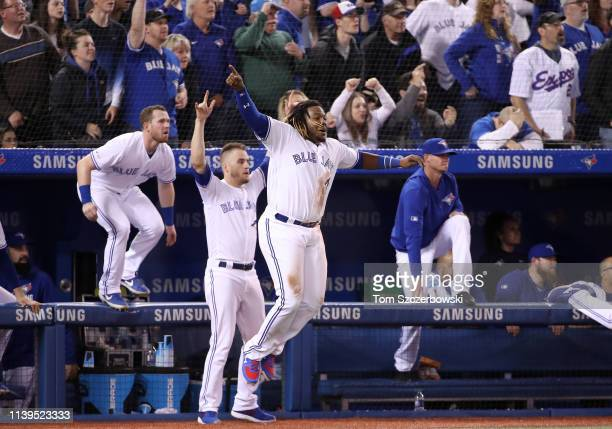 Vladimir Guerrero Jr #27 of the Toronto Blue Jays celebrates their victory with Billy McKinney and Ken Giles as Brandon Drury hit a gamewinning...