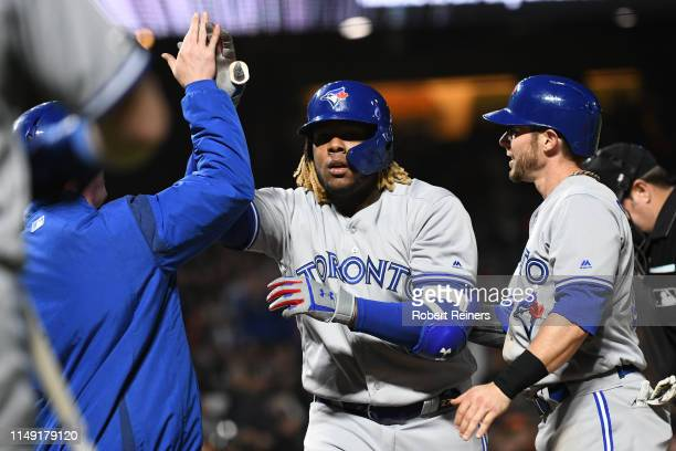 Vladimir Guerrero Jr #27 of the Toronto Blue Jays celebrates with Trent Thornton and Eric Sogard after hitting a threerun home run against the San...
