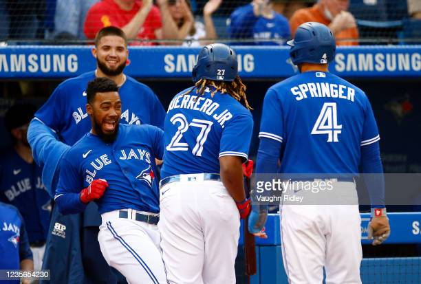 Vladimir Guerrero Jr. #27 of the Toronto Blue Jays celebrates with Teoscar Hernnadez after hitting a two-run home run in the first inning during a...