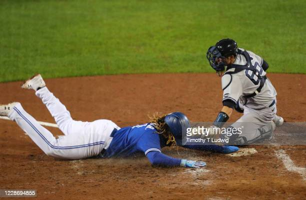 Vladimir Guerrero Jr. #27 of the Toronto Blue Jays dives safe to home plate as Kyle Higashioka of the New York Yankees misses the tag during the...