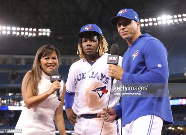Vladimir Guerrero Jr #27 of the Toronto Blue Jays does an interview with Hazel Mae of Sportsnet as interpreter Hector Lebron stands by following...