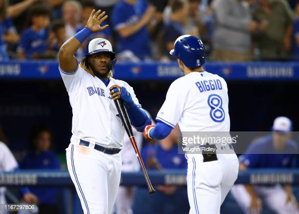 Vladimir Guerrero Jr #27 of the Toronto Blue Jays high fives Cavan Biggio after Biggio hit a home run in the third inning during a MLB game against...