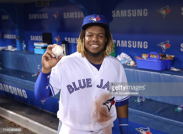 Vladimir Guerrero Jr #27 of the Toronto Blue Jays holds the baseball he hit for his first MLB career hit during MLB game action against the Oakland...