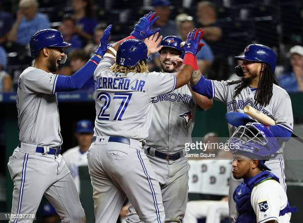 Vladimir Guerrero Jr #27 of the Toronto Blue Jays is congratulated at home plate by Lourdes Gurriel Jr #13 Randal Grichuk and Freddy Galvis after...