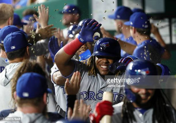 Vladimir Guerrero Jr #27 of the Toronto Blue Jays is congratulated by teammates in the dugout after hitting a grand slam home run during the 9th...