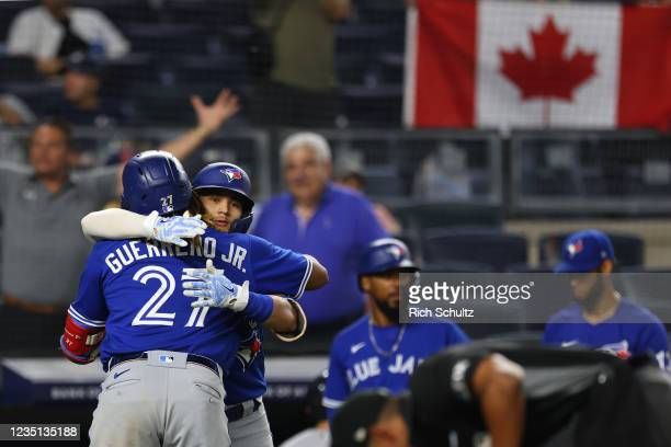 Vladimir Guerrero Jr. #27 of the Toronto Blue Jays is hugged by Bo Bichette against the New York Yankees during the ninth inning of a game at Yankee...