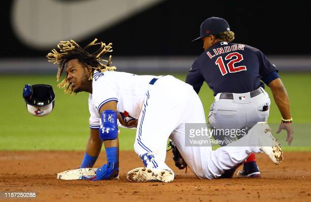 Vladimir Guerrero Jr #27 of the Toronto Blue Jays is tagged out by Francisco Lindor of the Cleveland Indians at second base in the second inning...