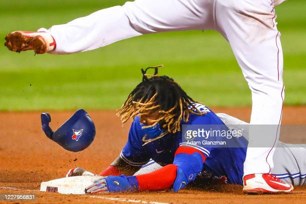 Vladimir Guerrero Jr #27 of the Toronto Blue Jays loses his helmet as he is tagged out as he slides head first into third base in the sixth inning of...