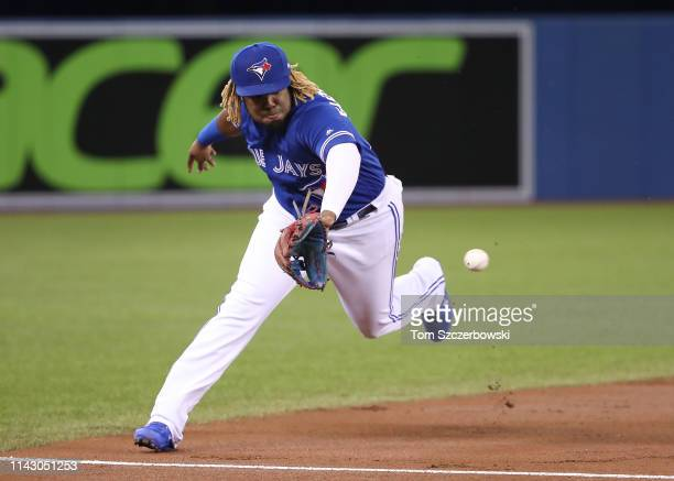 Vladimir Guerrero Jr #27 of the Toronto Blue Jays makes a defensive play and throws out the baserunner in the first inning during MLB game action...