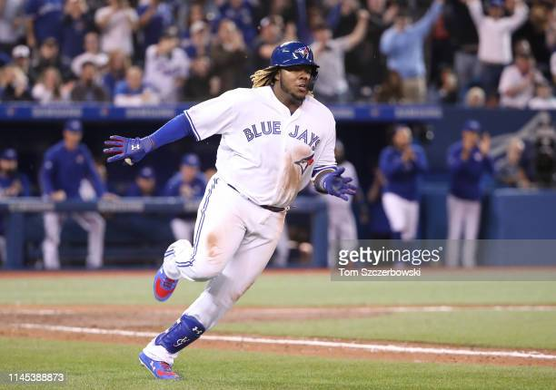 Vladimir Guerrero Jr #27 of the Toronto Blue Jays runs to first base as he hits a double for his first career MLB hit in the ninth inning during MLB...